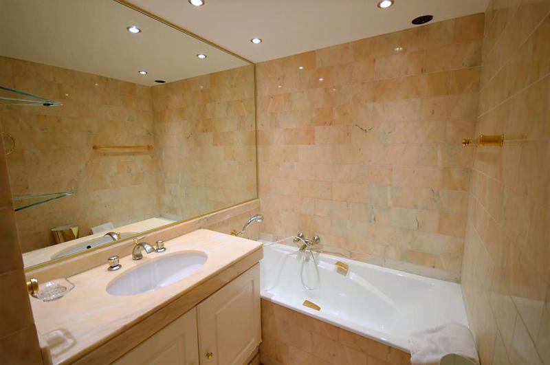 Mustard coloured rectangular tiles and white bathtub in a bathroom with large mirror in Cannes
