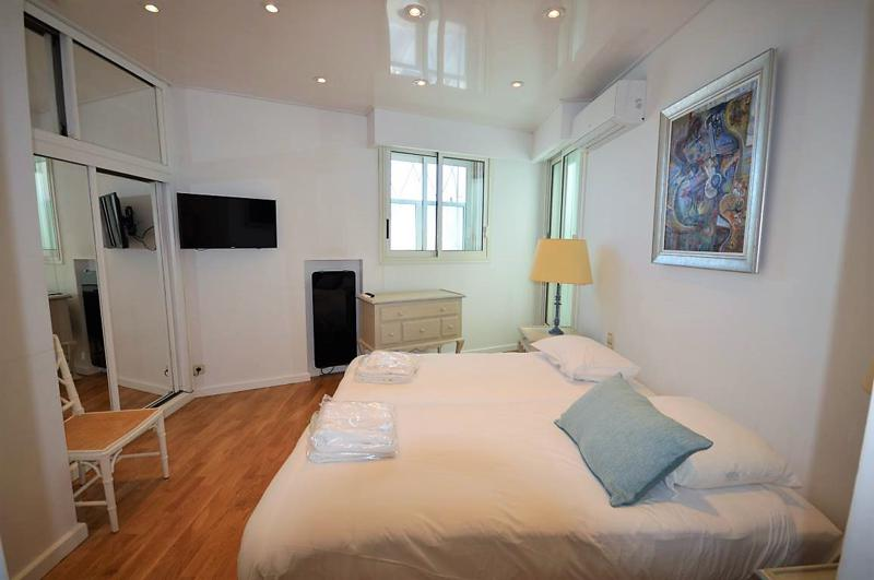 2 singles beds with a painting on the wall behind, a mirror in front, a chair and a wall mounted flat screen tv