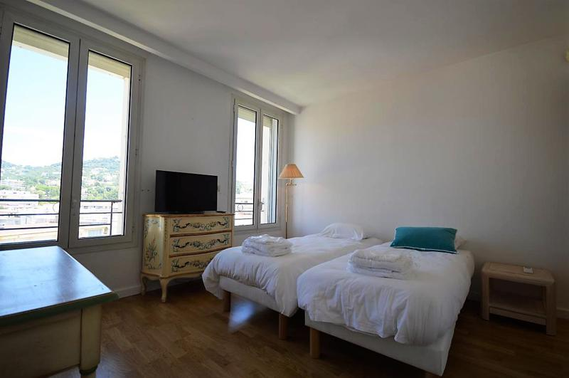 2 single beds in a wooden floored room with white walls, a flat screen tv and views of Cannes from the window