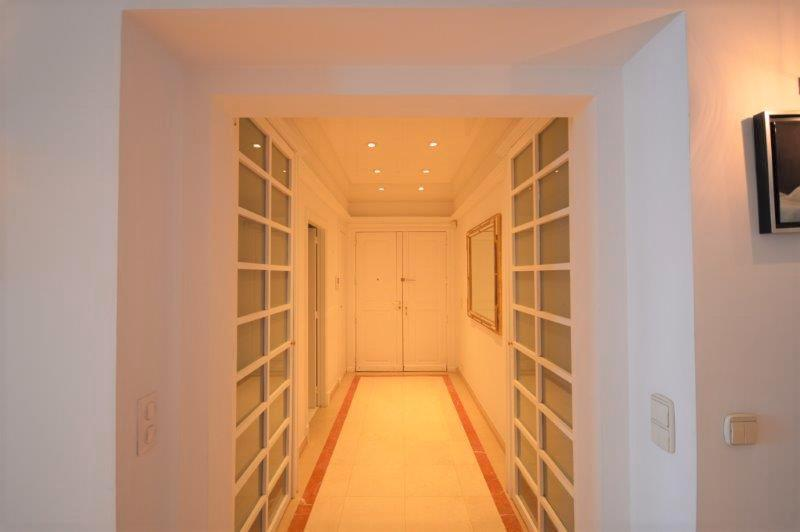Entrance hallway with yellow lights, white walls and doors in an apartment