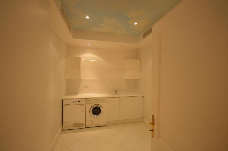 Laundry room with white washing machine and cabinets in Cannes