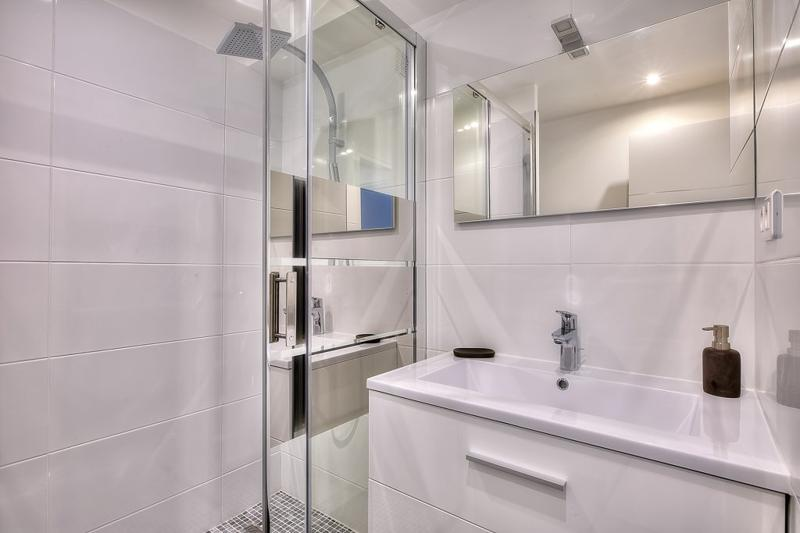 A standing shower with a sliding glass door separating the sink in a bathroom with white tiles