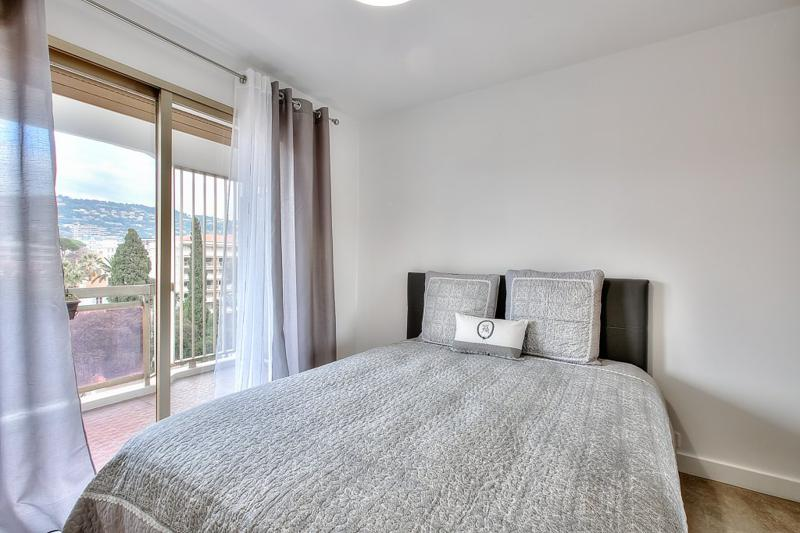 Double bedroom with a sliding glass door leading to the terrace with views in a Cannes event accommodation