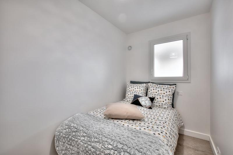 Single bed in a white painted room with a window