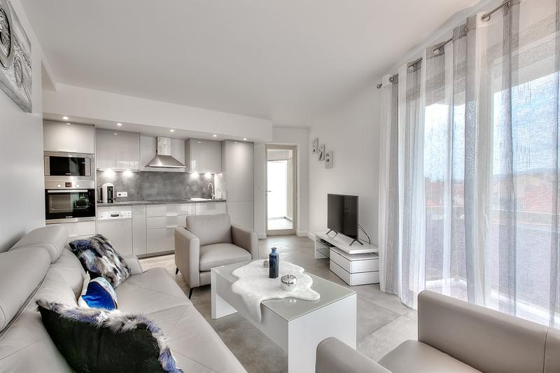 Open kitchen and couches in the living room of a 3 bedroom Cannes group apartment with terrace near to the Convention centre