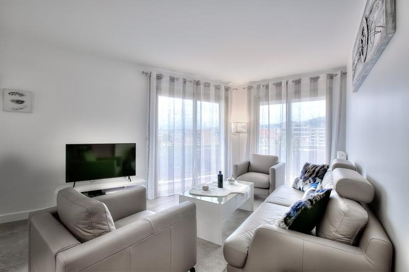 Living room with cream leather couch set, a flat screen tv and views of the city in a Cannes rental apartment