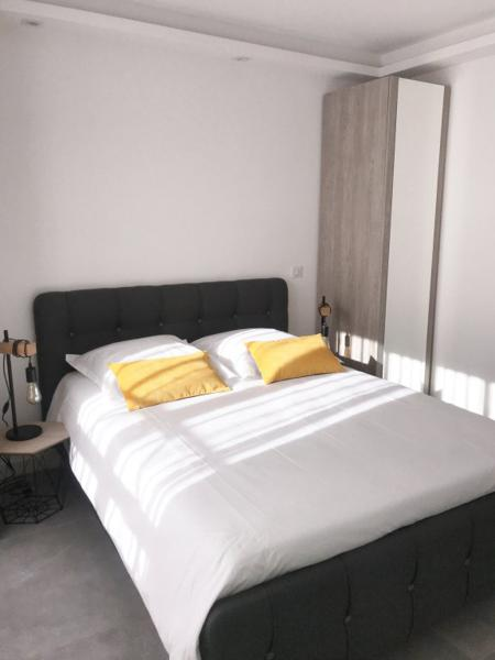 Double bedroom with white sheets and 2 side tables with lamps in a 3 Bedroom Cannes rental accommodation on Rue Marceau