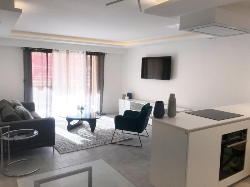 Couch set in the living room with natural sunlight and an open kitchen with an oven in Cannes group rental apartment