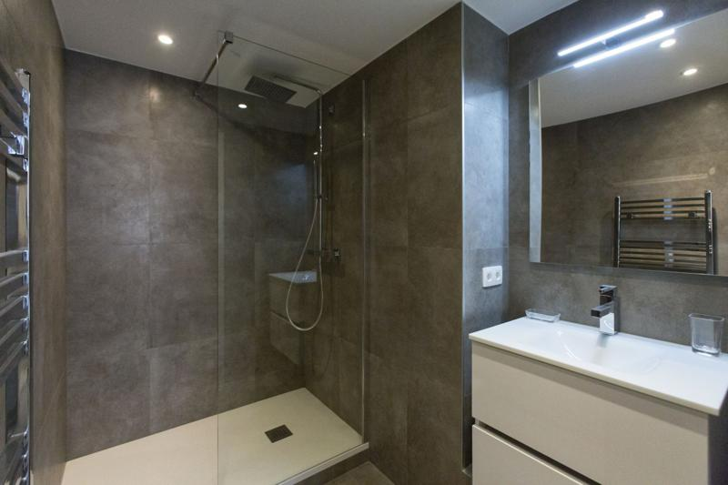 Glass enclosed standing shower and sink with mirror