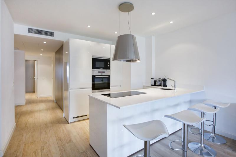 Wooden flooring in a Cannes group apartment by the sea with microwave, coffee maker and stools in the white open kitchen
