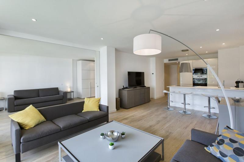 Living room with brown couches, a sofa bed, a flat screen tv and an open kitchen with stools in Cannes apartment for rent