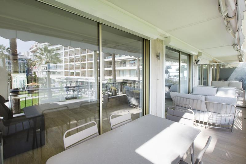 Dining table and couches for relaxing on the terrace of a 3 bedroom Cannes event apartment by the sea
