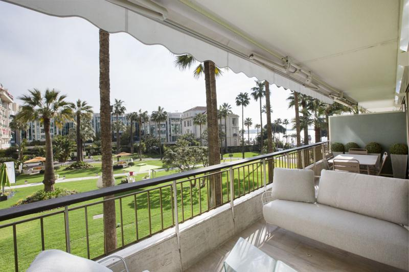 White couches and table with chairs for meetings on the terrace overlooking the garden and sea in a Cannes rental apartment