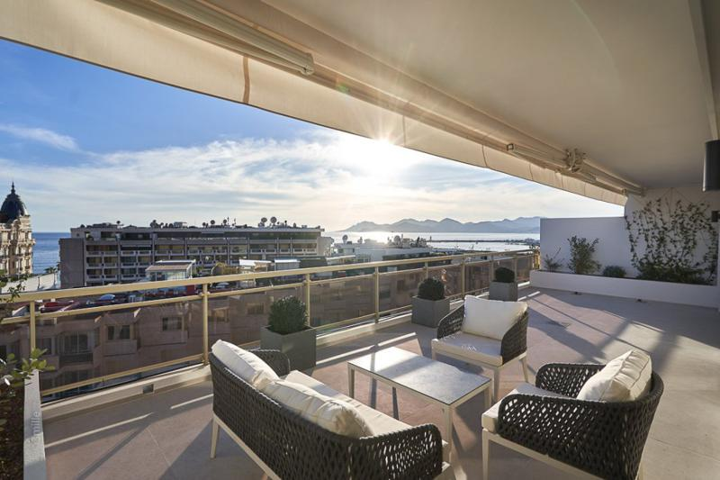 Panoramic views of Cannes and the sea from a spacious terrace with furniture set in a Cannes event penthouse for rent