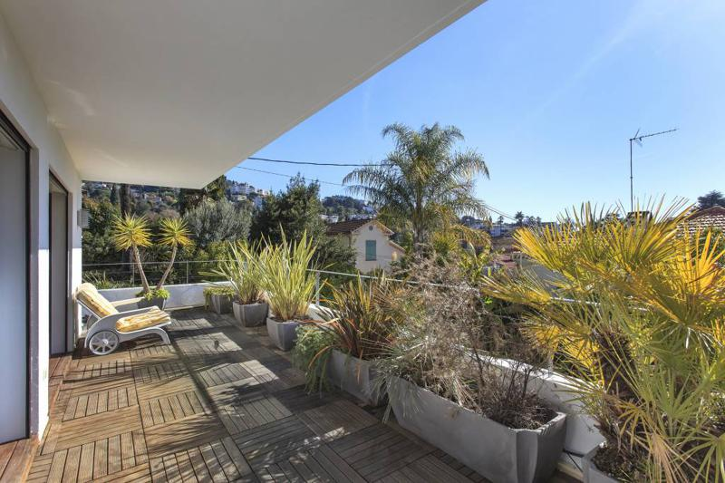 Terrace with wooden deck, plants and surrounding views of landscapes in a Cannes group event Villa