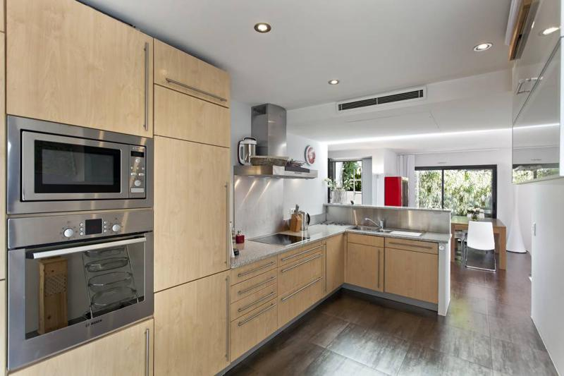 Kitchen with wooden cabinet doors, microwave and an oven in a Cannes villa