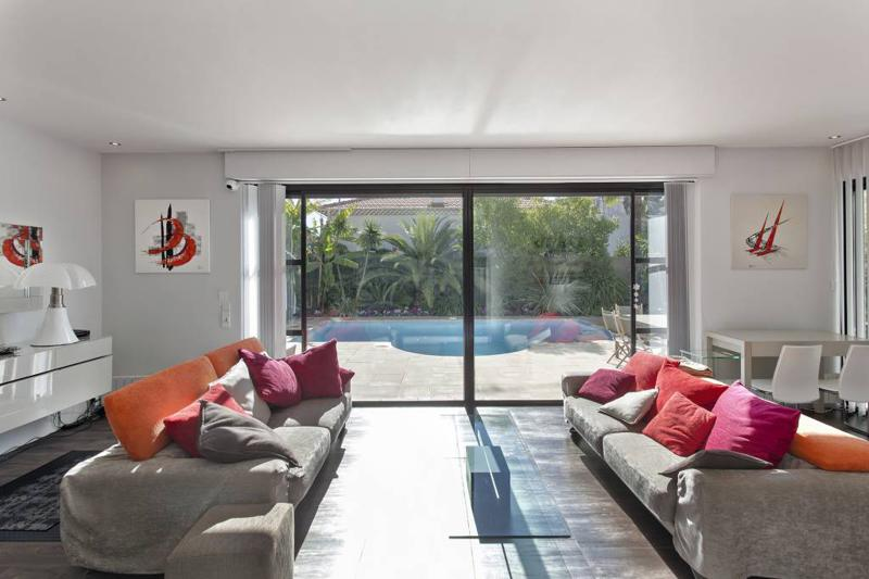 2 couch sets with red, pink and orange cushions in the living room of a Cannes event villa with swimming pool