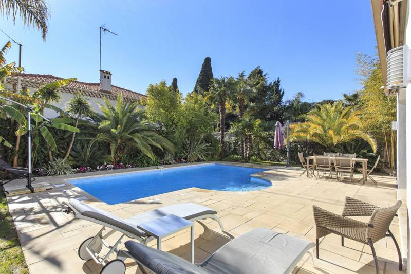Relaxing area with lounge chairs and dining table next to the swimming pool in Cannes group villa close to the beach