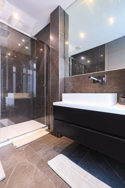 Large wall mirror, standing shower and sink in the bathroom
