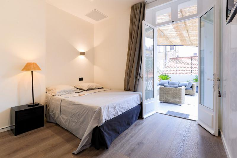 Double bedroom opening to outdoor terrace with couches and view of the city in Cannes group accommodation
