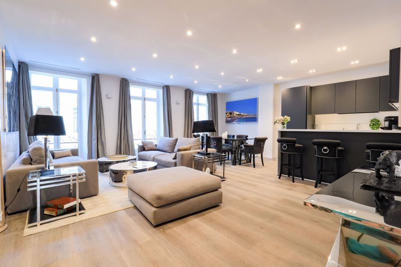 Furnished living room with dining area, open kitchen and flat screen tv in a Cannes group accommodation on Rue Hoche