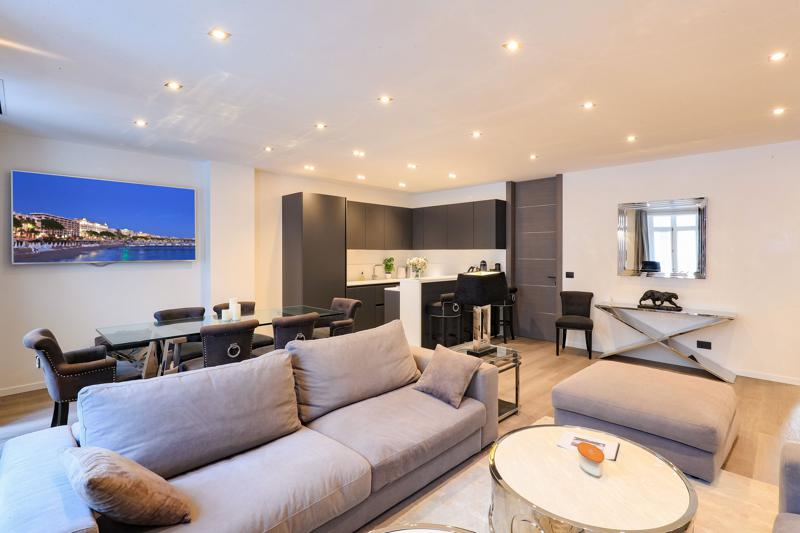 Living room with beige couches, mounted tv, open kitchen and dining table in Cannes apartment close to Palais des Festivals