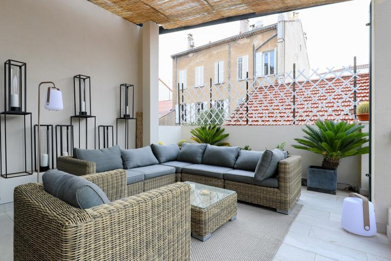 Wicker couches and table in the terrace with lamps, candles, plants and view of buildings of a Cannes group event apartment