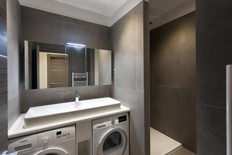 2 washing machines in a grey themed laundry room of a Cannes rental apartment