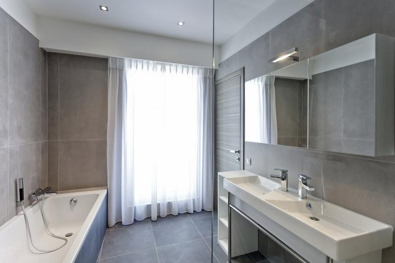 glass door covered by white curtains in a bathroom with bathtub
