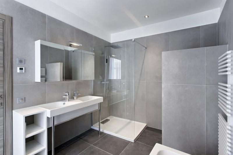 Dark grey and white interiors in the spacious bathroom with standing shower in a Cannes apartment