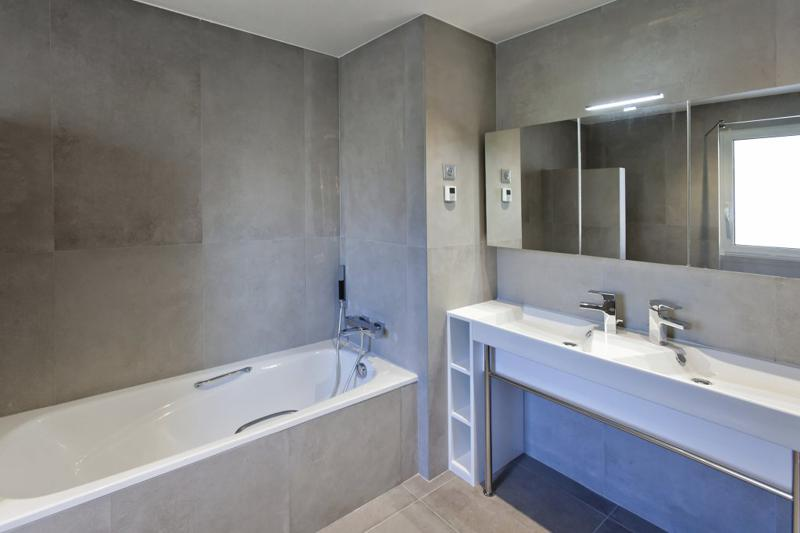 Grey interiors in a bathroom with bathtub and dual sink with mirror in Cannes