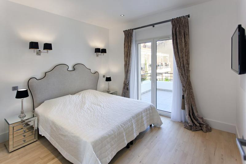 Wooden flooring in a double bedroom with a tv and a private terrace in Cannes rental apartment