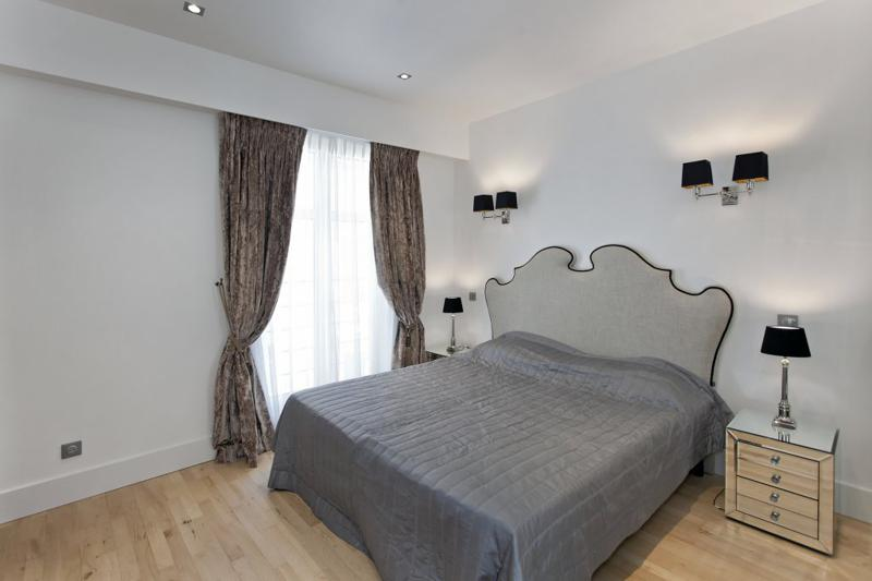 Double bed in a bedroom with wooden floor and access to the balcony with views in Cannes