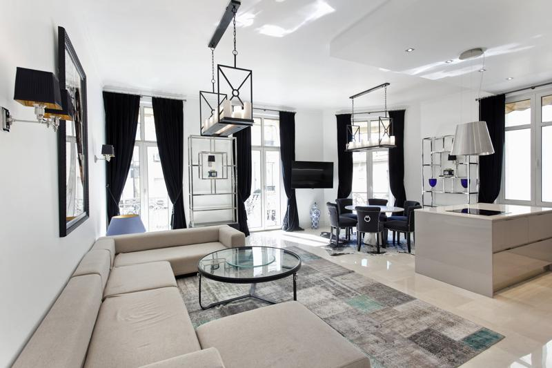Spacious living room with black, white and beige coloured interiors in a 4 bedroom modern Cannes rental apartment for groups