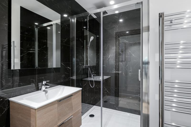 Glass-enclosed standing shower with black marble walls and a sink in Cannes