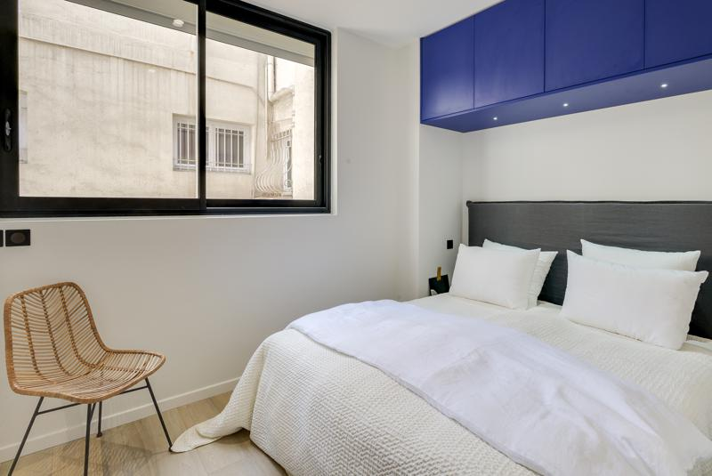 Wooden flooring in a double bedroom with white pillows and covers, a blue painted shelf and a chair