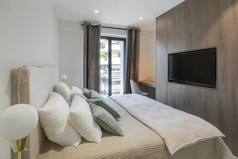 Double bedroom with a pillows and covers, private terrace, a wall mounted tv, and a desk and a chair in Cannes