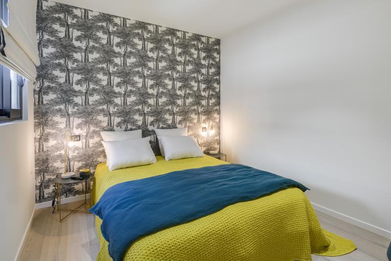 White pillow, yellow sheet and blue blanket in a Cannes double bedroom with a side table and a wallpaper.