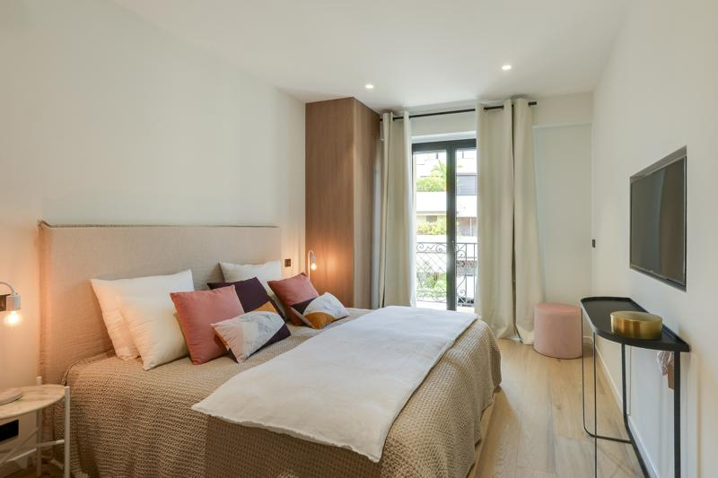 Double bedroom with a private balcony, a tv, pillows and covers in a Cannes rental apartment