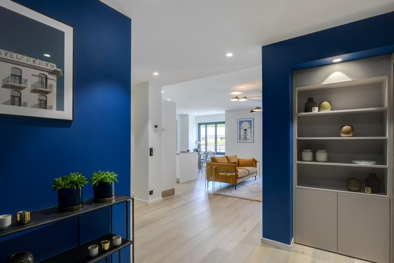 Blue painted walls in the gallery of a Cannes group apartment with a view of the couch in the living room