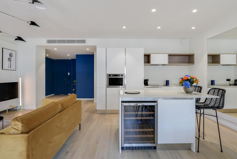 Open kitchen with mini fridge and bar stools in a Cannes group rental apartment with white and blue interiors