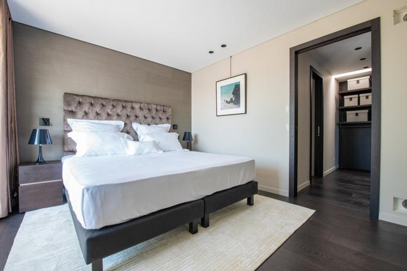 Double bed with white covers and pillows, natural sunlight and a walking closet in Cannes rental penthouse.