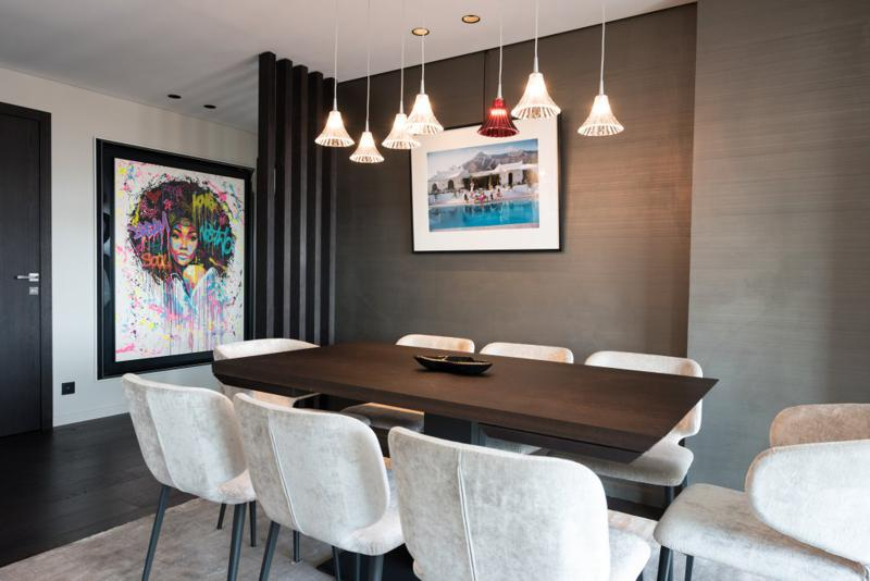 Dining table with velvet chairs and wall paintings in a Cannes group penthouse