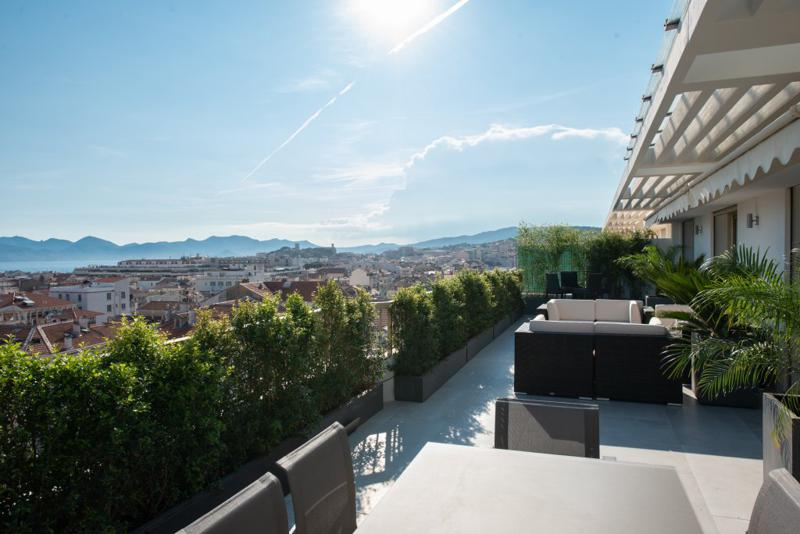 Views of sea, city and mountains from the terrace of a 4 bedroom Cannes party penthouse with an outdoor lounge