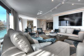 Cream coloured couch sets in the living room of a luxurious Cannes party apartment for rent near the conference centre.