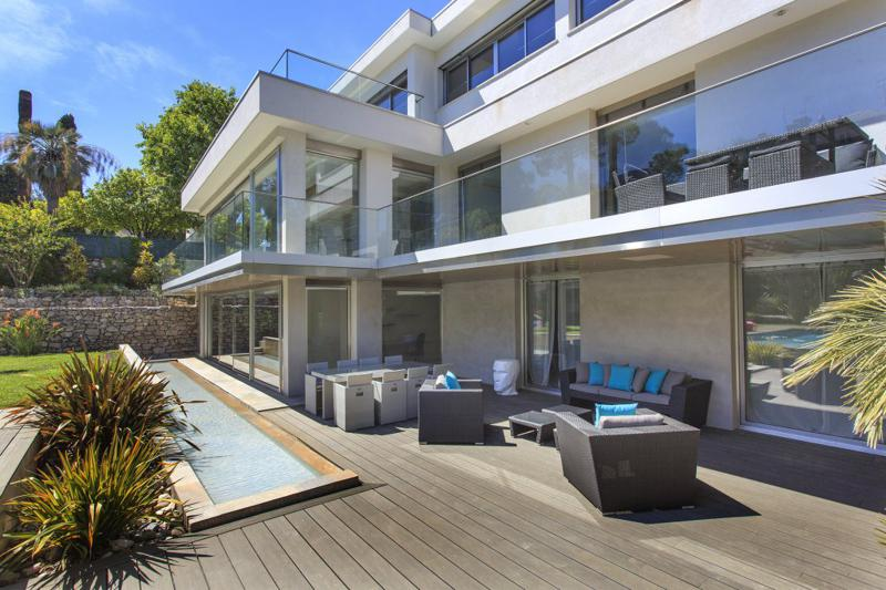 Couches and dining table on the deck outside the living room in a Cannes group rental villa for events