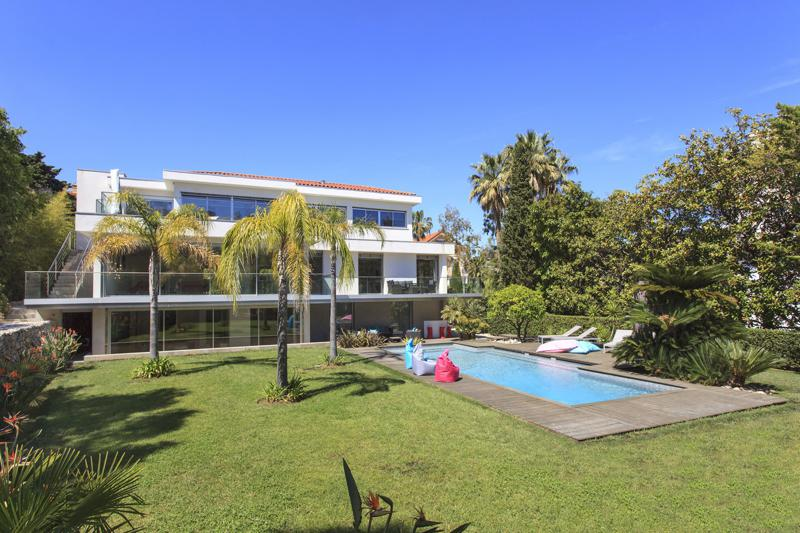 5 bedroom Cannes party villa with a relaxing area on the outdoor deck surrounded by a garden and swimming pool in the centre