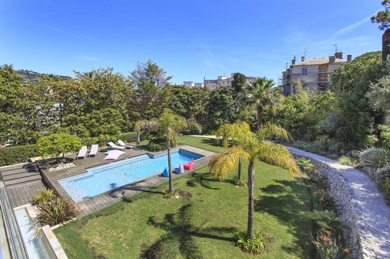 Terrace view of a garden with palm trees and swimming pool surrounded by outdoor relaxing furniture in a Cannes rental villa