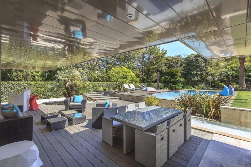 Outdoor deck with couches, tables, stools, lounge chairs and swimming pool for events and parties in a Cannes rental villa