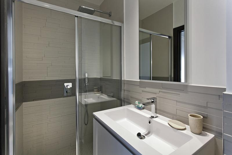 Bathroom with a standing shower and a sink and mirror
